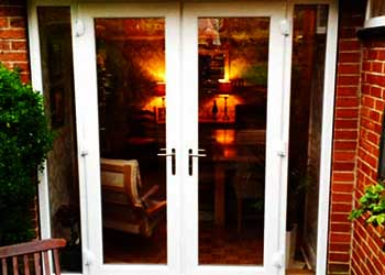 photo of double frnech doors from the outh side dimly lim from the inside finished in crisp white with floor to top glass panes and a just a very small but solid looking frame