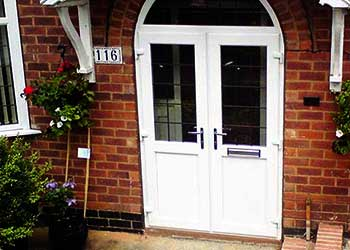 Distance view of a home front double main eantrance doors with a small roof all in white pvcu