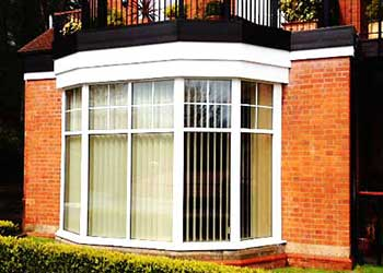 close up view of a stinning pvcu bay window with 10 large glass panes and 20 small square panes in the windows top panels finished in crisp white