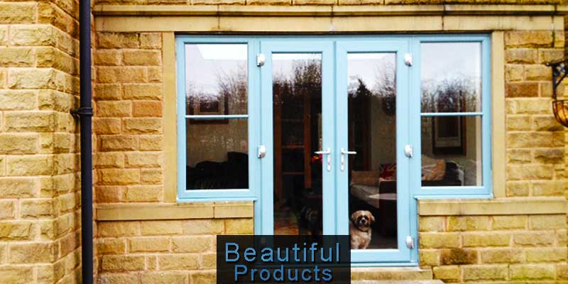 stunning replacement double frenceh doors in aqua blue with atached side windows on a stone built home